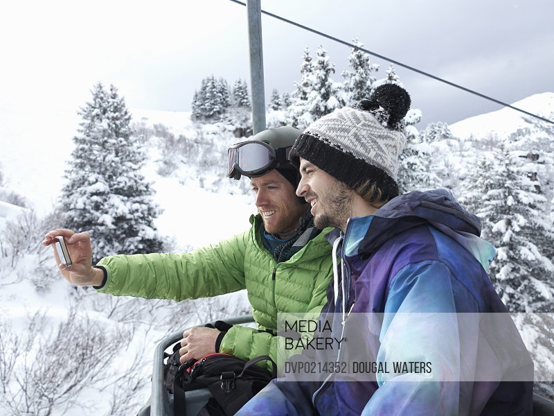 Two friends use a mobile phone to take their picture in The Alps