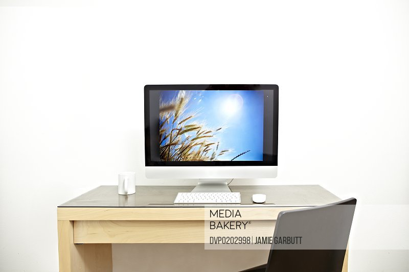 Computer on a desk with a white mug