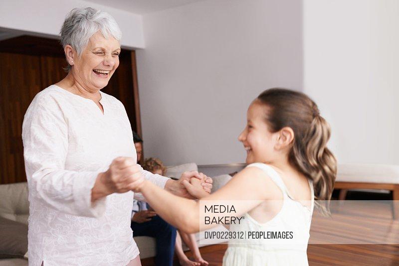 A grandmother and granddaughter dancing