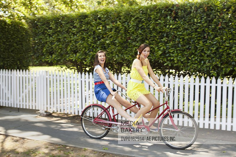 Two young women in sun dresses and high heels ride a vintage red tandem bicycle. They are riding on a residential sidewalk in the suburbs in front of a white picket fence and hedges.