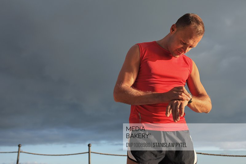 Man checking time during jogging against stormy sky