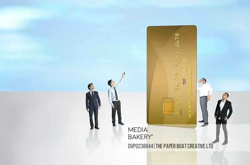 Group of businessmen near a giant credit card