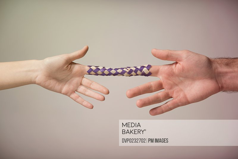 Young man and woman's hands with Chinese finger trap attached to index fingers
