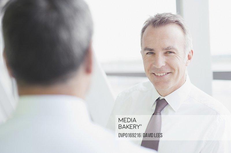 Businessmen in meeting smiling