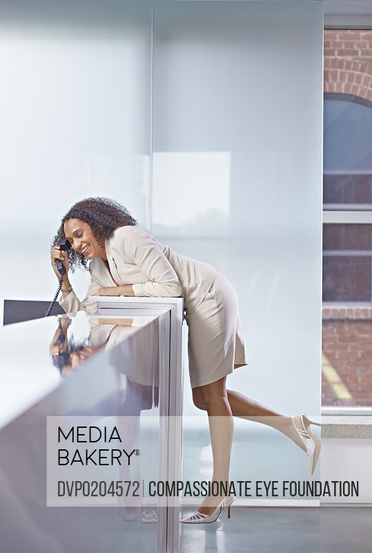 Businesswoman leaning over desk on telephone