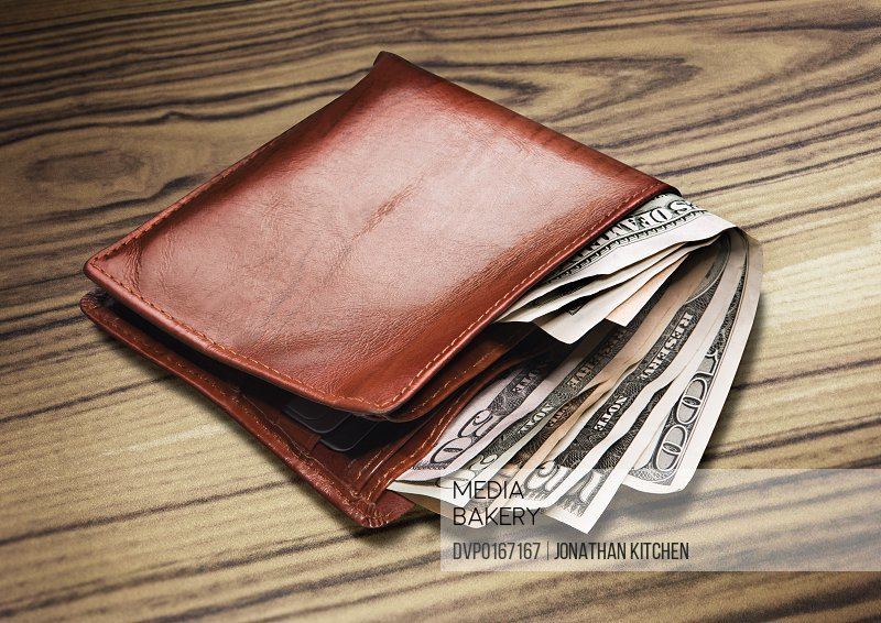 a wallet with Dollar Notes currency on a wooden background