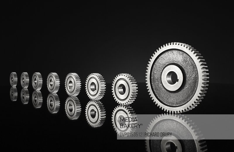 Small cogs following big cog on black background