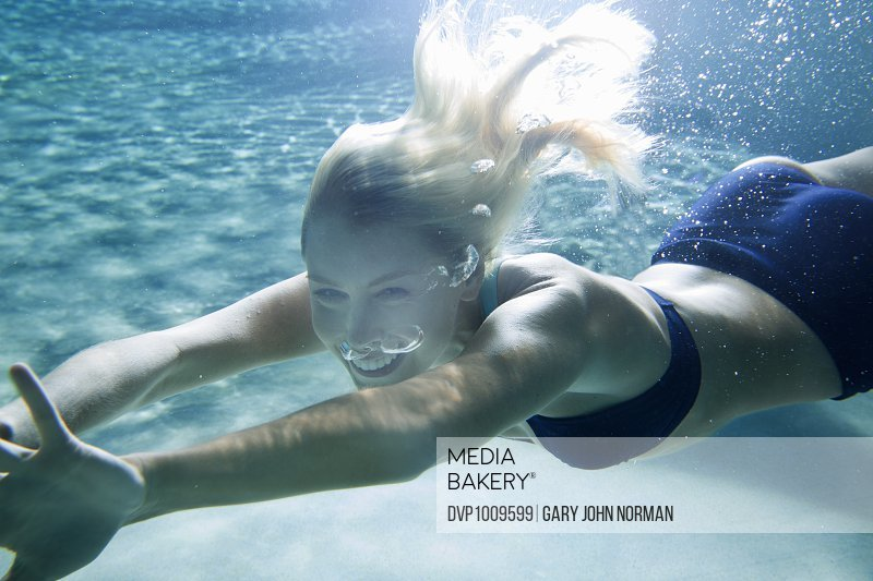 Young woman swimming underwater, smiling at camera