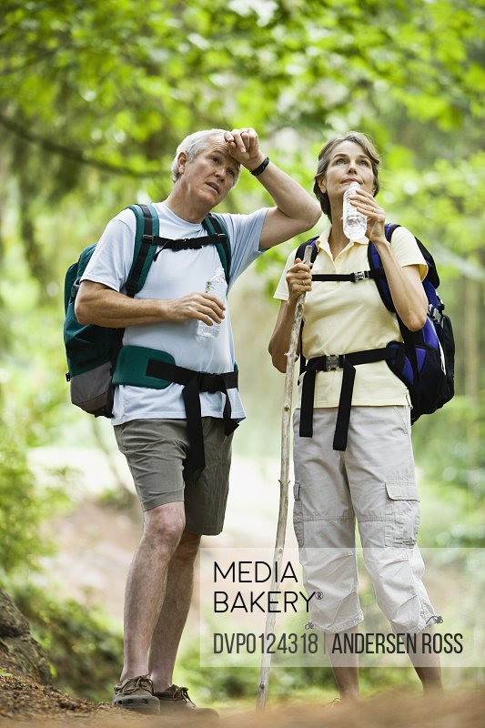 Mature couple taking break while hiking through forest