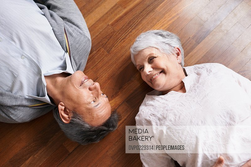 Shot of a happy-looking elderly couple lying down and smiling at each other