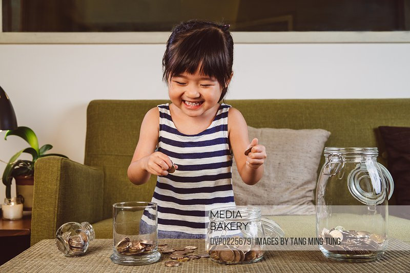 Child putting coins in different glass jars