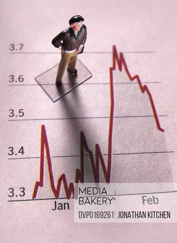 A man stands on a financial page of a stock market listing