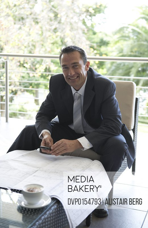 Portrait of businessman using Blackberry style mobile communication device with building plans.