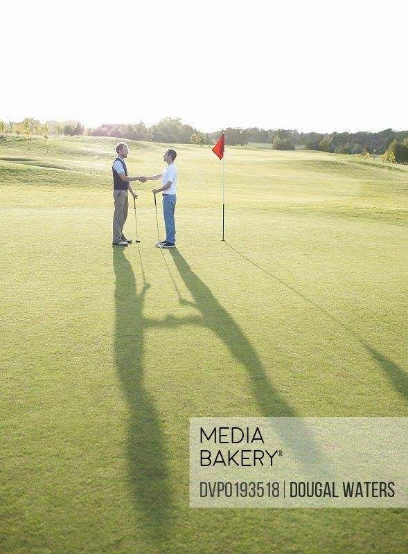 Men on golfing green shaking hands