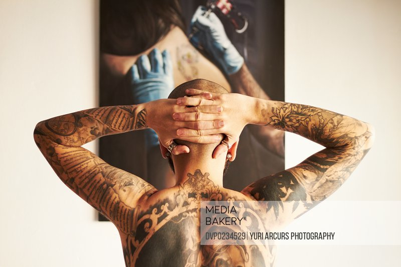 The back of a male with tattoos along his back with his hands on his head