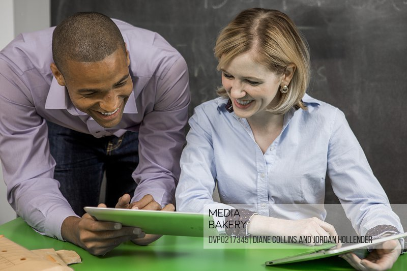 two young adults using technology in office