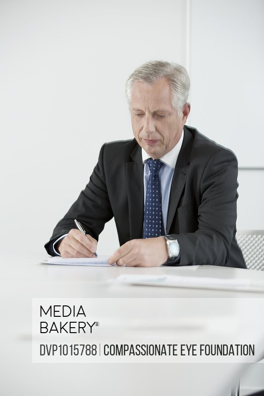 Mature businessman reviewing paperwork in office