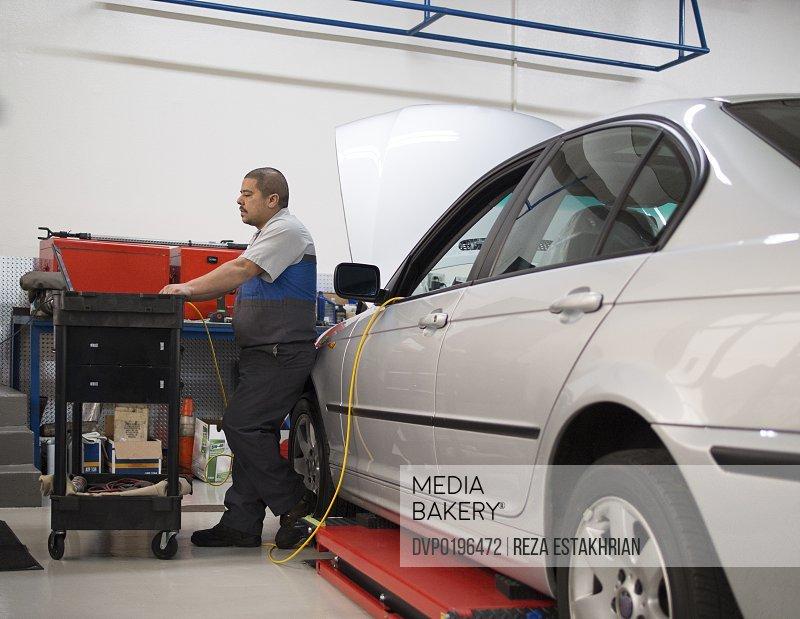 Mechanic checks diagnostics on auto