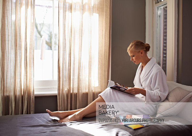 Shot of a beautiful young woman reading magazines while sitting on her bed