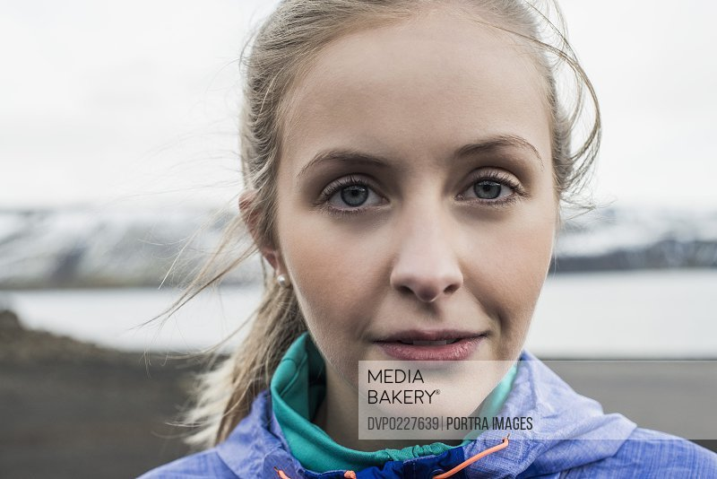 Close-up portrait of sporty woman by lake