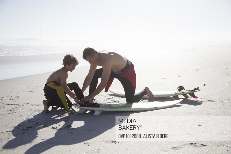 Father and son preparing surf boards on a beach