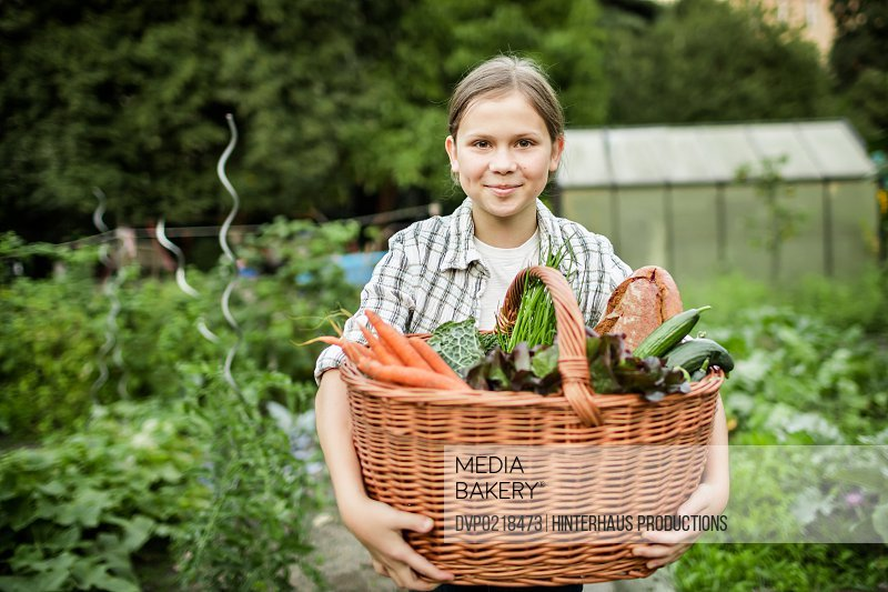 Young girl presenting her freshly harvested vegetable and food