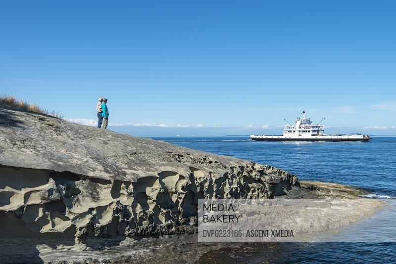 Senior couple stand on coastal rocks watch ferry