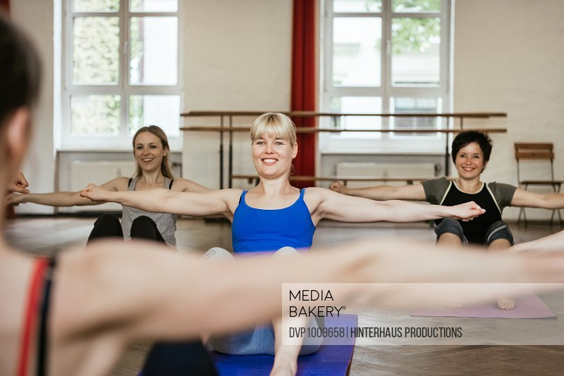 Women in workout class sitting on floor and training abdominals