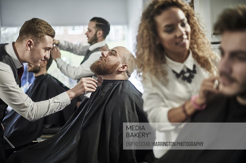 Barber giving beard trim in busy barbers shop