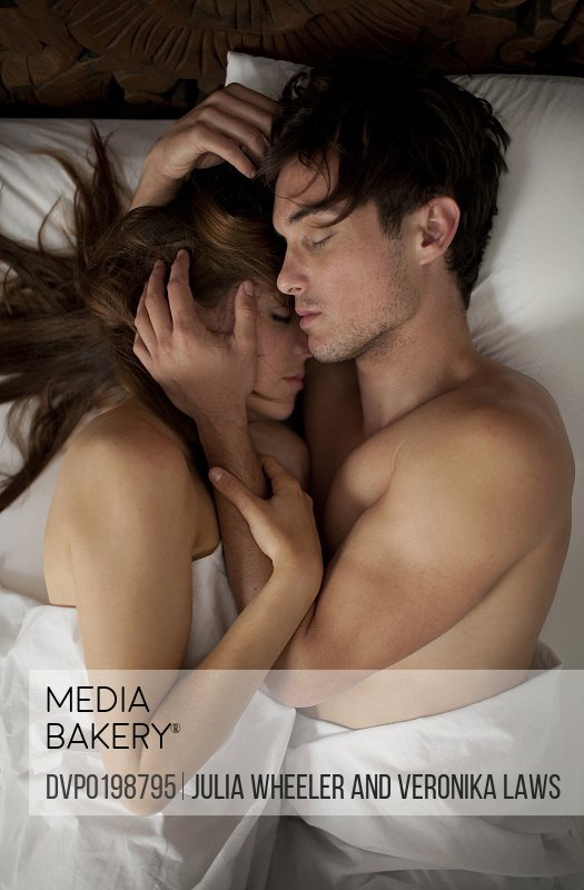 Couple asleep cuddling intimately in bed