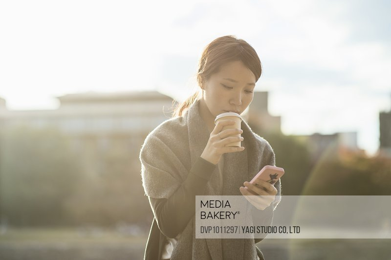 Woman using smartphone and drinking coffee