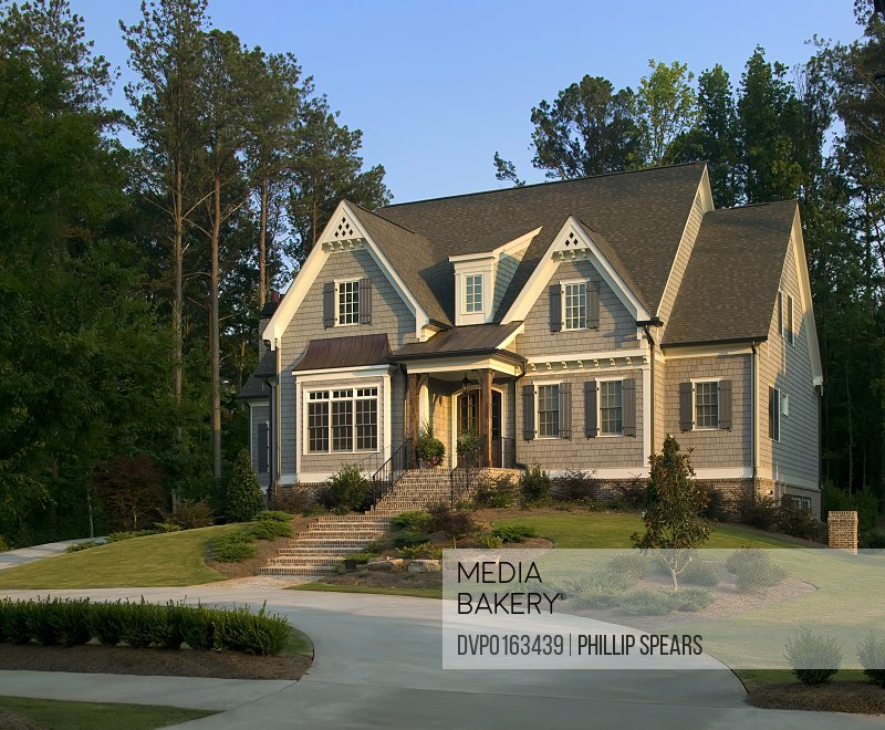 Traditional Suburban House with landscaped lawn.
