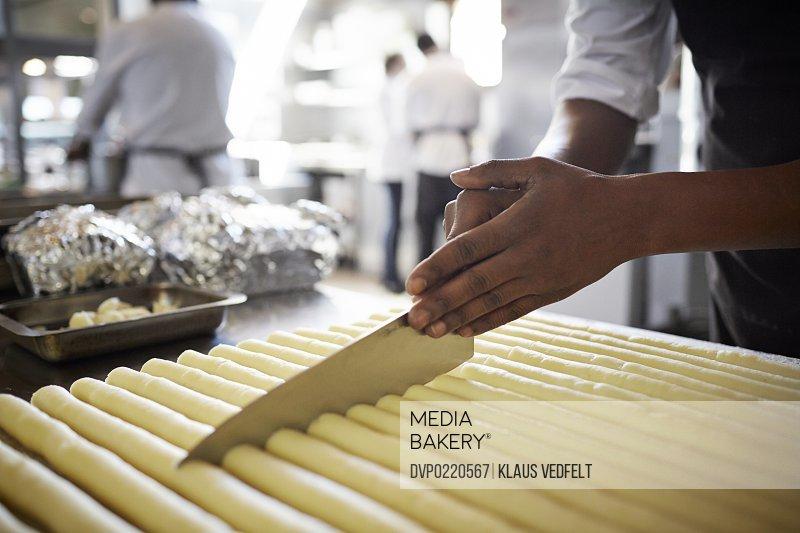 Chef cutting dough in kitchen at restaurant