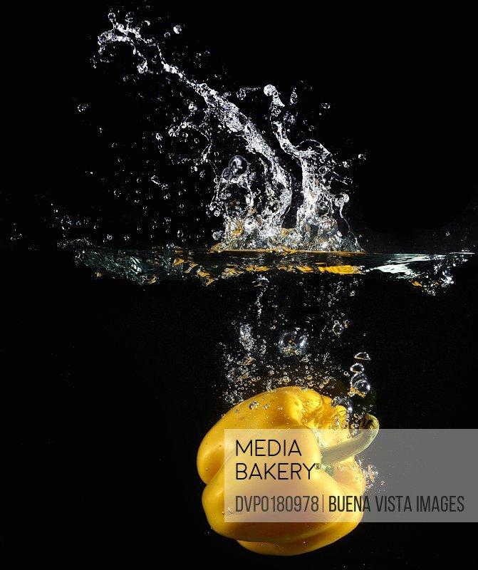 Yellow pepper splashing in water