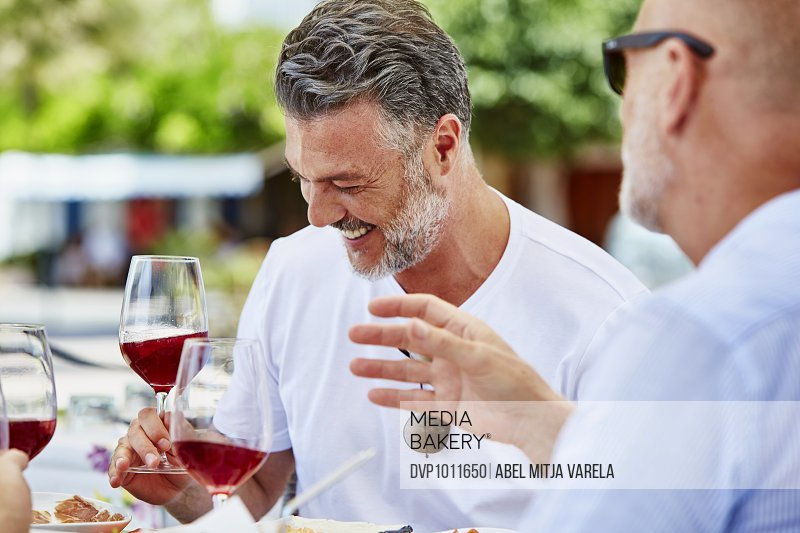 Happy man having red wine with friend