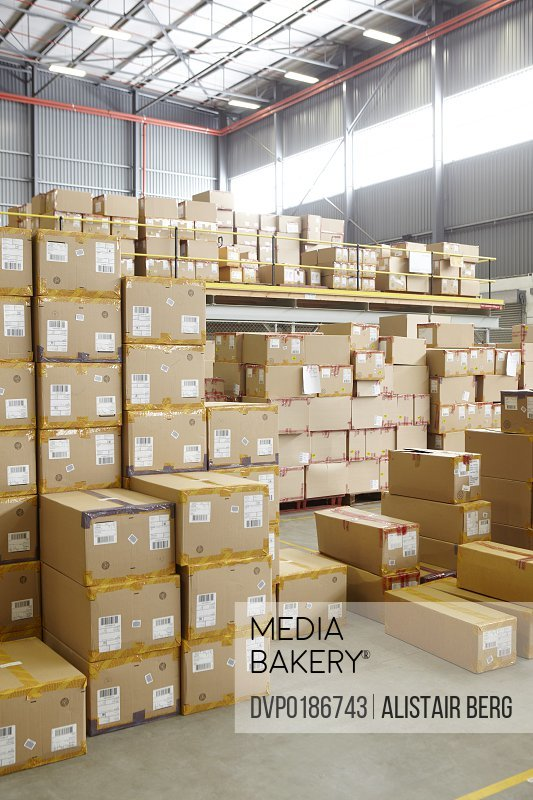 View of aisle in modern warehouse storing boxes of clothing