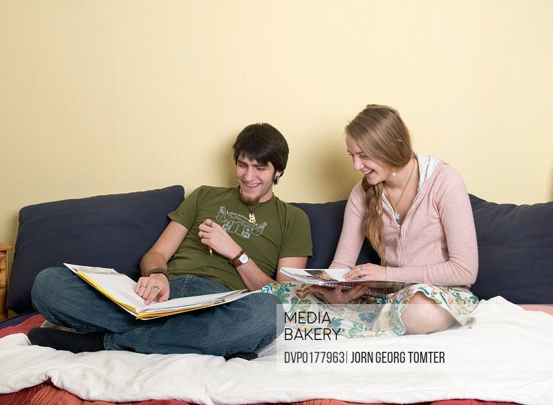 Couple 18-25 years old sitting in bed during the day reading or revising and laughing