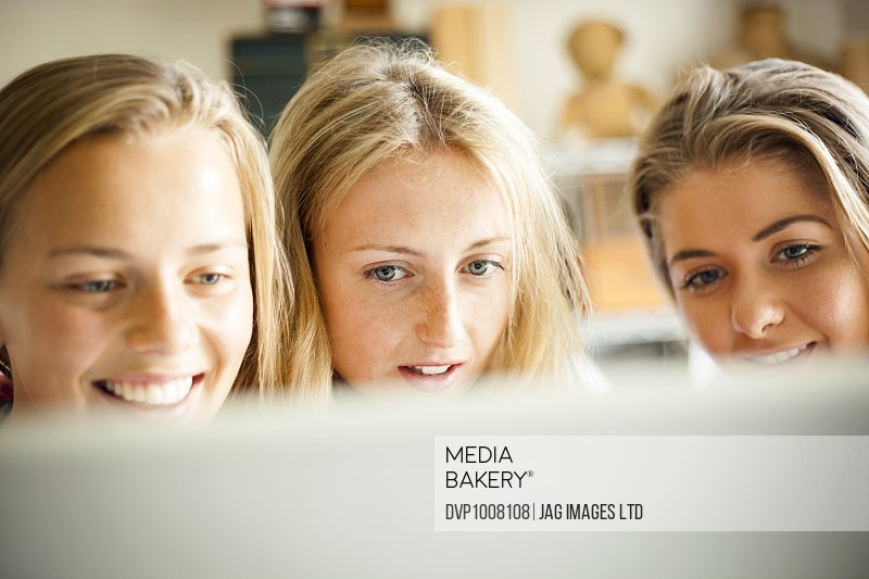 young women , revising , studying , working using books , writing and using the computer in home office