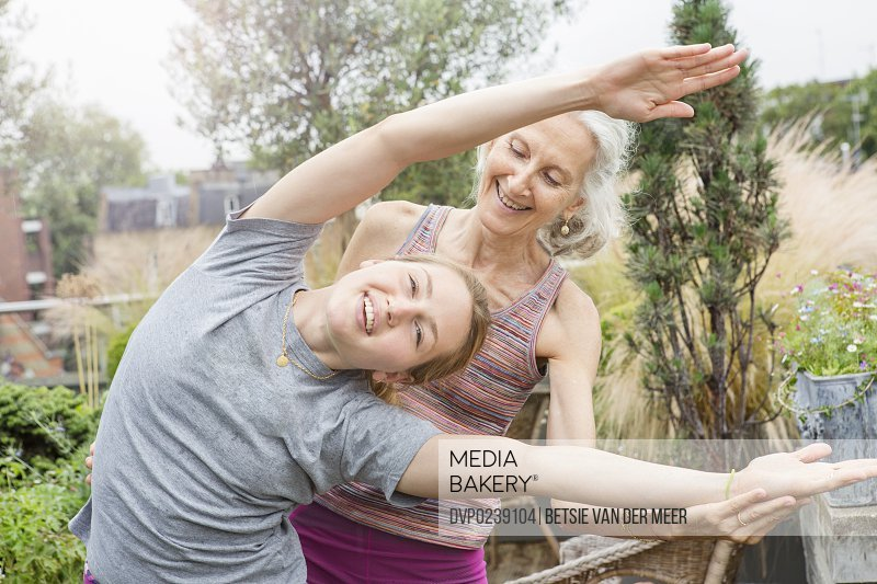 Senior woman helps young woman with yoga stretch