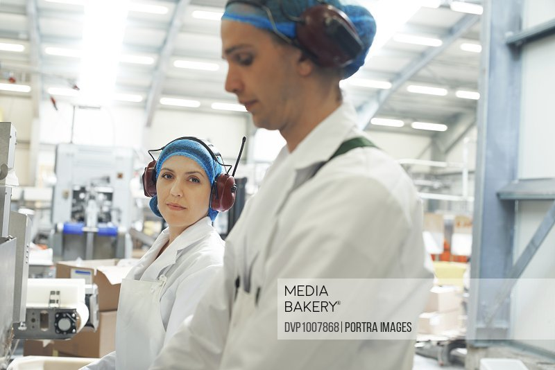 Portrait of confident female worker wearing ear protectors while working with coworker in fishing industry