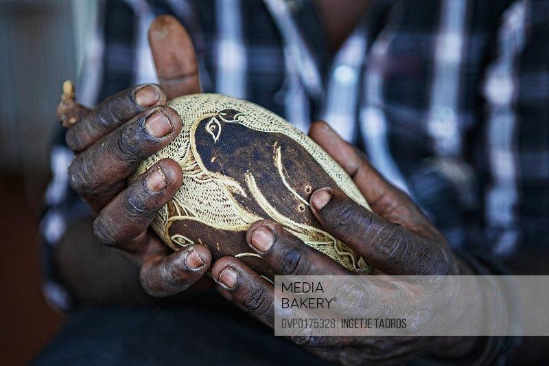 Hands holding carved boab nut