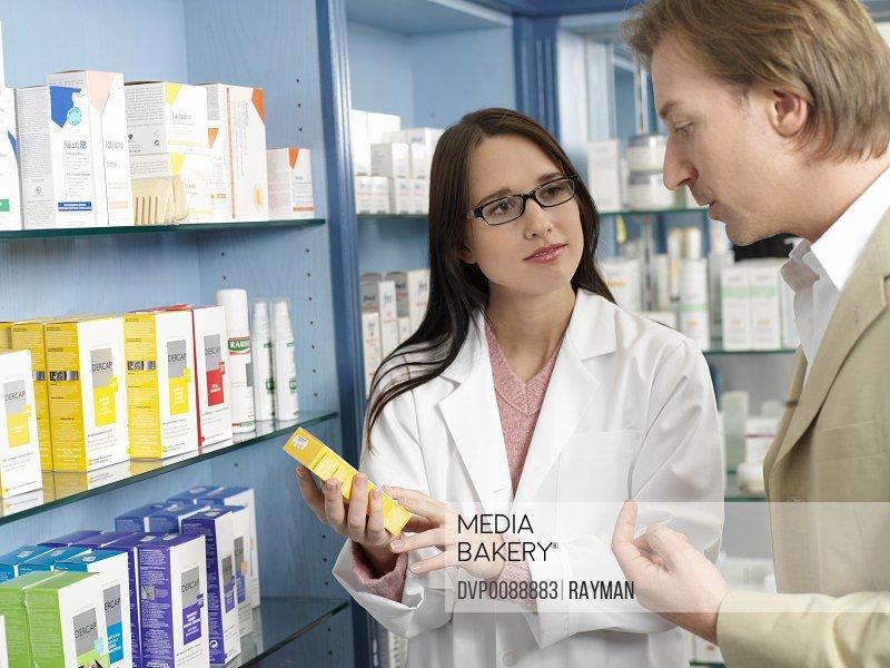 Pharmacist showing medicine to customer