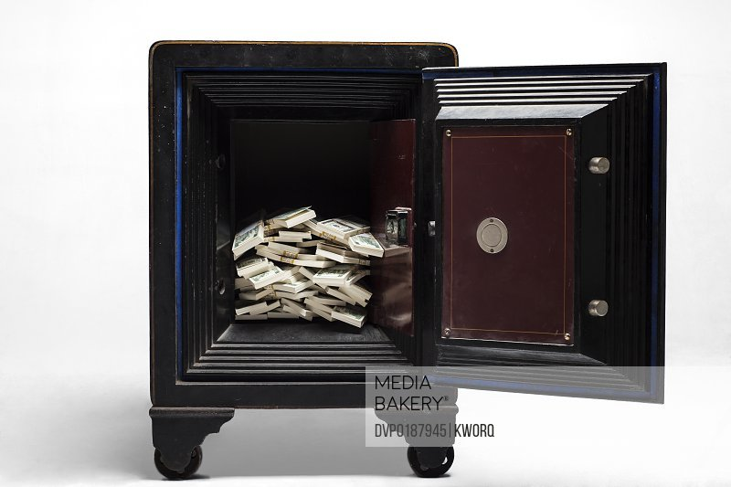 Open safe shot in studio on white background with stacks of cash in it