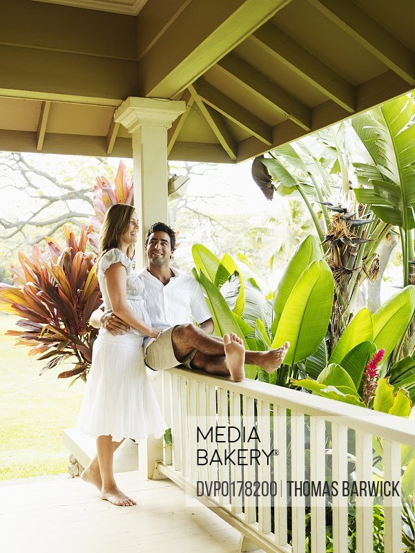 Couple embracing on front porch of tropical home