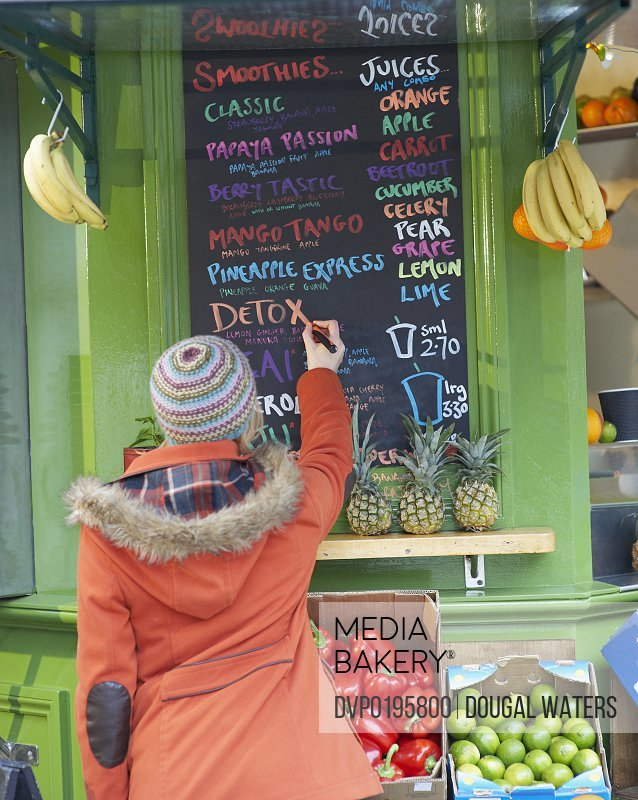 Woman writing on sign at juice bar