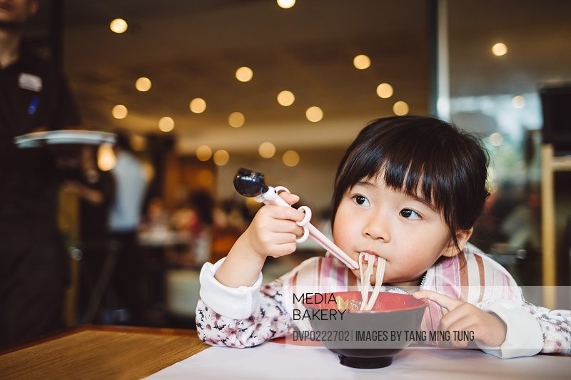 Little girl having noodles in restaurant