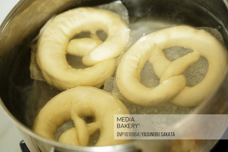 Pretzels of dough in hot water