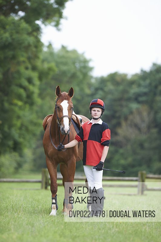 Young jockey standing with horse