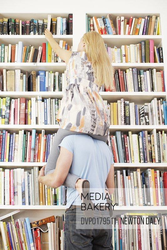 Man giving woman piggyback to reach book