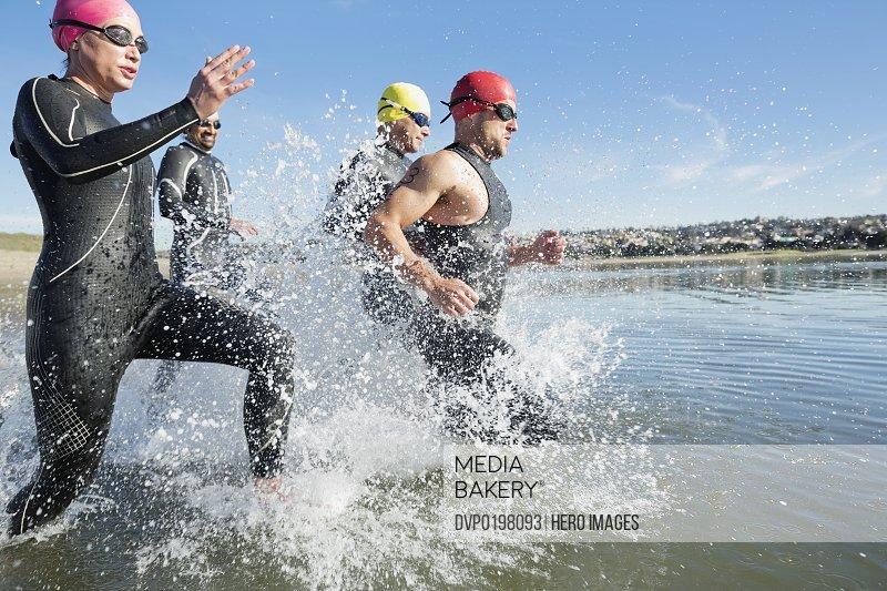 Triathletes running into water